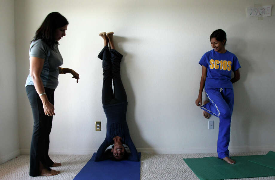 "Shamim Kanscwala teaches Alina Jaffer, 12, to do a headstand as her sister Ftima Jaffer, 13, watches during a yoga class at  ""Camp Eco.logic,"" a three-day winter break camp for teens, kids are learning about agriculture, food waste and climate change. Photo: Helen L. Montoya, San Antonio Express-News / ©SAN ANTONIO EXPRESS-NEWS"