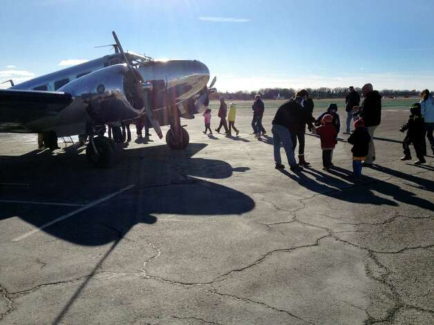 Sandy Hook Elementary School students and their parents tour a 1940s-era Beechcraft Model 18 at the Sikorsky Memorial Airport in Startford, Coon. on Friday, Dec. 28, 2012. Volunteers with the Connecticut Air and Space Center helped organize the visit to the airport to give the students a day of fun after the Newtown shooting two weeks ago. Photo: Drew Joseph, Drew Joseph/Hearst Newspapers / Connecticut Post