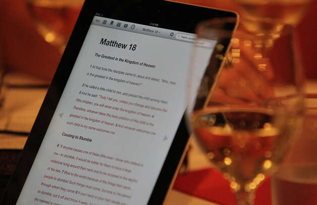 "The Book of Matthew is shown on an iPad surrounded by glasses of wine. Rev. Steve Coker of The Light Mission Community heads up the ""Wine in the Word"" bible study fellowship at Wine 101 in Bulverde, Texas on Wednesday, Feb. 15, 2012. On the first Wednesday of each month, Coker leads a group in a spiritual discussion over glasses of wine. Coker said he's trying to reach out to those who may not be the typical Sunday morning worship participant. The group is open to anyone and to all denominations. Kin Man Hui/San Antonio Express-News Photo: Kin Man Hui, San Antonio Express-News / San Antonio Express-News"
