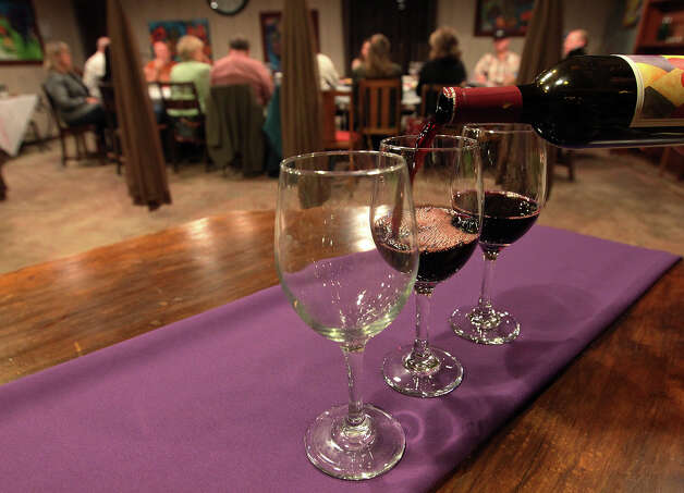 "Wine is poured for members of the bible study group. Rev. Steve Coker of The Light Mission Community heads up the ""Wine in the Word"" bible study fellowship at Wine 101 in Bulverde, Texas on Wednesday, Feb. 15, 2012. On the first Wednesday of each month, Coker leads a group in a spiritual discussion over glasses of wine. Coker said he's trying to reach out to those who may not be the typical Sunday morning worship participant. The group is open to anyone and to all denominations. Kin Man Hui/San Antonio Express-News Photo: Kin Man Hui, San Antonio Express-News / San Antonio Express-News"