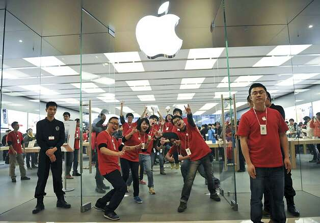 Chinese employees pose for photographers at the newly opened Apple Store at the MixC mall in Chengdu in southwest China's Sichuan province on Saturday, Dec. 15, 2012. Apple Computer currently has eight stores in mainland China. (AP Photo) CHINA OUT Photo: Associated Press