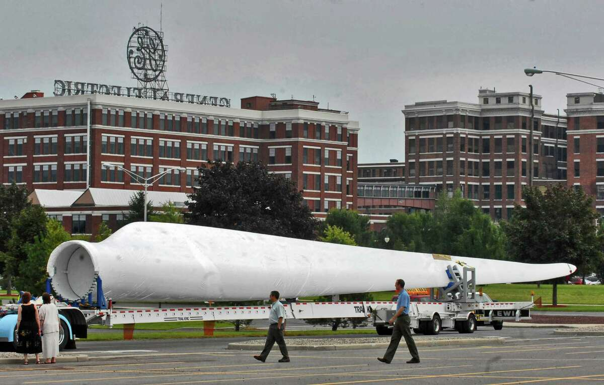 Onlookers check out the newly arrived 121-foot long wind turbine blade at GE?s Schenectady, NY campus on Wednesday August 26, 2009, in preparation for display there. The big blade was shipped from Newton, Iowa. , Friday, August 21, traveling with wide-load escort vehicles. The blade will be placed near the solar panel installation behind the newly renovated Building 53, which houses the GE Renewables Global Headquarters.The grand opening of this new facility will be held later this autumn. (Philip Kamrass / Times Union)