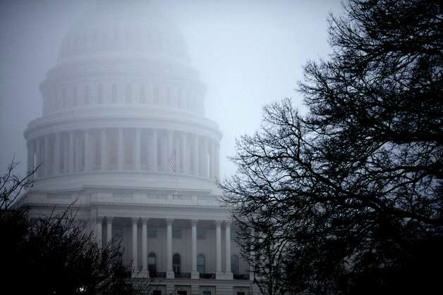 "In this Dec. 10, 2012 file photo, fog obscures the Capitol dome on Capitol Hill in Washington. A safe route around the ""fiscal cliff"" continues to elude Congress and the White House. A recession is possible if automatic tax increases and spending cuts begin to take effect on Jan. 1, and people are afraid. But stock mutual fund managers remain optimistic that there will be significant rewards for staying invested in stocks. Photo: J. Scott Applewhite, Associated Press / Associated Press"