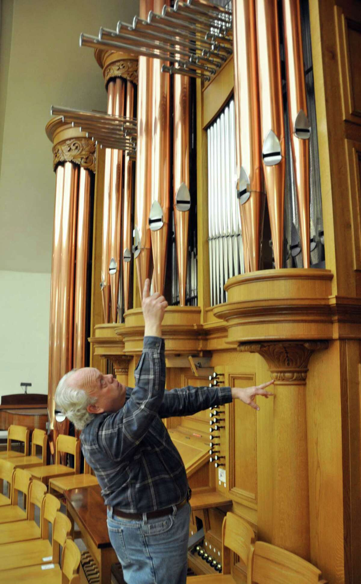 In this Friday, Nov. 30, 2012 photo, organ builder John Nordlie points at some of the towering pipes on an instrument he built for First United Methodist Church, in Sioux Falls, S.D. The pipe organ has ruled the Christian worship sanctuary for centuries, but a growth in praise-band worship services and a nationwide shortage of qualified organists are prompting many congregations to leave the majestic instrument out of their new building construction plans. But organ aficionados say they see a bright future for the instrument. (AP Photo/Dirk Lammers)