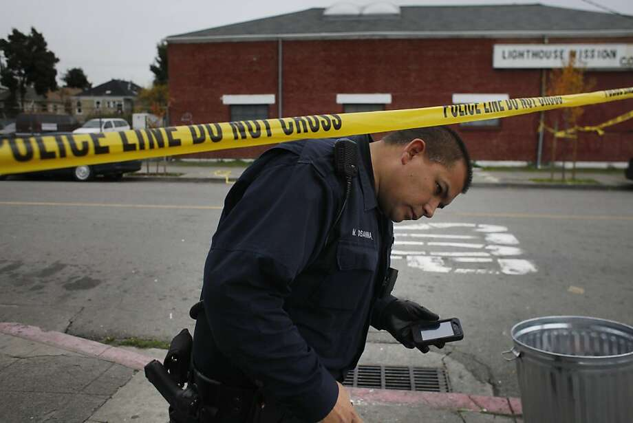 Officer Michael Osanna investigates the shooting deaths of two men on Mead Avenue. Photo: Lacy Atkins, The Chronicle