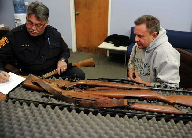 John Coppola, of West Haven, watches Officer Pete Garcia log his three rifles and a shotgun, two of which were used in WWII, during a gun buyback event at the Bridgeport Police Department's Community Services Division Friday, Dec. 28, 2012 in Bridgeport, Conn. In the wake of the tragedy in Newtown, Conn., the city raised $100,000 for the program and will offer up to $200 value for a working handgun, $75 for rifles and higher amounts for assault-type rifles.  The buy back will continue every Saturday until the city gives out all of the funds which includes an additional $10,000 in gift cards from the Food Bazaar grocery store. Photo: Autumn Driscoll / Connecticut Post