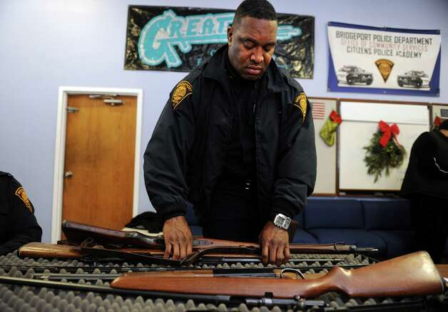 Bridgeport Police Officer Roger Reid moves rifles returned during a gun buyback event at the Bridgeport Police Department's Community Services Division Friday, Dec. 28, 2012 in Bridgeport, Conn. In the wake of the tragedy in Newtown, Conn., the city raised $100,000 for the program and will offer up to $200 value for a working handgun, $75 for rifles and higher amounts for assault-type rifles.  The buy back will continue every Saturday until the city gives out all of the funds which includes an additional $10,000 in gift cards from the Food Bazaar grocery store. Photo: Autumn Driscoll / Connecticut Post