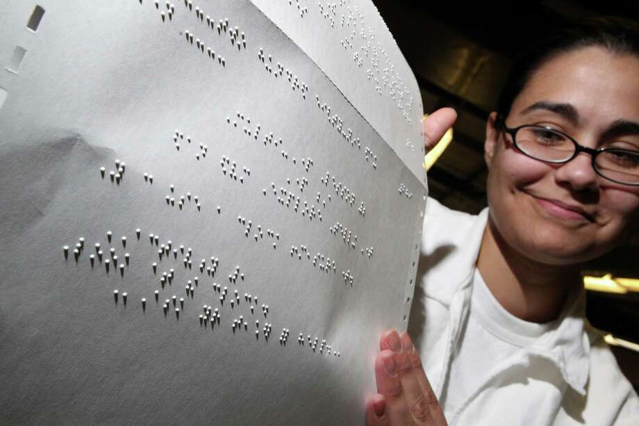 Holding a page of Braille text, Alexa Garza, 33, who is serving 20 years for murder, works with the digital tactile graphics in the Braille facility at the Mountain View Womens Prison where they translate textbooks into Braille for the blind. Photo: Johnny Hanson, Houston Chronicle / © 2012  Houston Chronicle