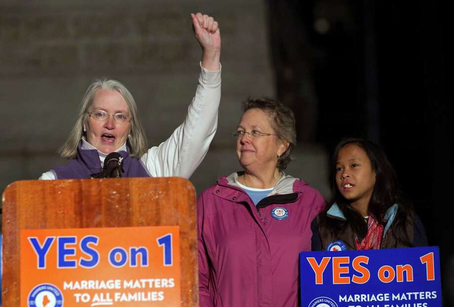 Sarah Dowling speaks at a Nov. 1 rally in Portland, Maine, accompanied by her partner of 18 years, Linda Wolfe, and their daughter, Maya Dowling-Wolfe. Dowling and Wolfe planned to marry at midnight, as soon as the law went into effect. Photo: Robert F. Bukaty, STF / AP