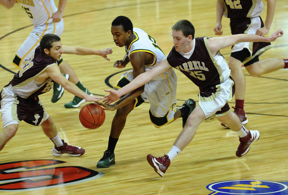 Monsignor Farrell's #21 James Rauitolo, left, and teammate #35 Brian Finnegan try to disrupt a drive by Trinity Catholic's #12 Tyrell St. john, during Northeast Christmas Classic basketball tournament at Webster bank Arena in Bridgeport, Conn. on Frday December 28, 2012.