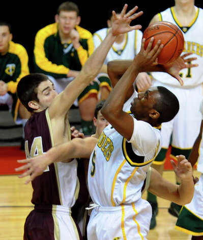 Trinity Catholic's #5 Brandon Wheeler attempts a shot as Monsignor Farrell's #44 Thomas Vazzana defends, during Northeast Christmas Classic basketball tournament at Webster Bank Arena in Bridgeport, Conn. on Frday December 28, 2012. Photo: Christian Abraham / Connecticut Post