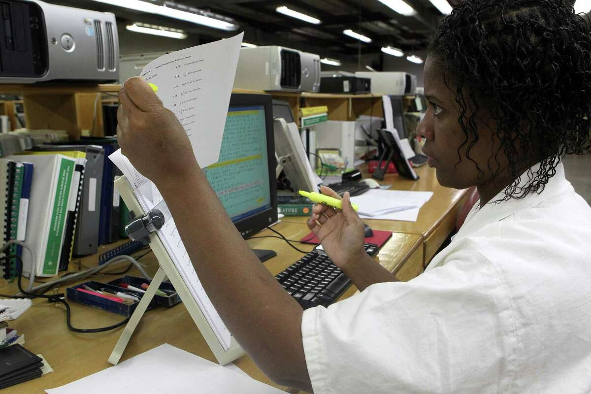 Lucretia Manuel, 37, who is serving a life sentence for capital murder of a child, proofreads a page. The unit produces 5,000 to 10,000 pages a month.