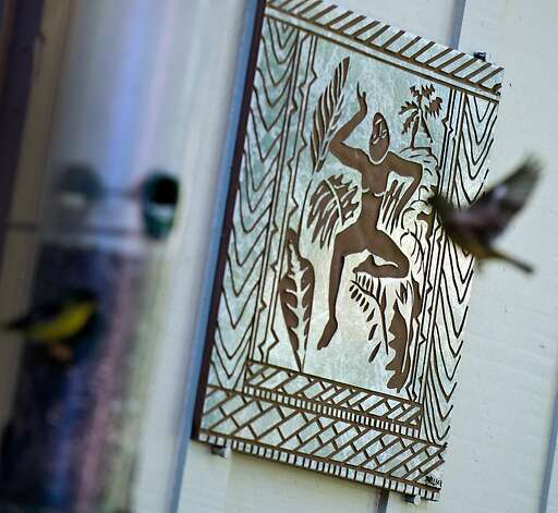 Gold finches fly to a bird feeder hanging near an artisan tile created by Donna Billick, of Billick Rock Art, at the home of Sheila Menzies and Joe Taylor, co-founders of the Tile Heritage Foundation, in Healdsburg, CA on October 17, 2012. Photo: Alvin Jornada, Special To The Chronicle