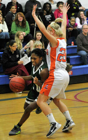 Brewster's Peyton Montague drives to the basket around Danbury's Lindsey Eanniello during The News-Times Greater Danbury Holiday Festival championship game at the Danbury War Memorial on Friday, Dec. 28, 2012. Danbury won, 53-24. Photo: Jason Rearick / The News-Times