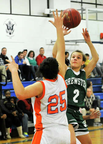 Brewster's Megan Lueder puts up a shot over Danbury's Kayla Handberry during The News-Times Greater Danbury Holiday Festival championship game at the Danbury War Memorial on Friday, Dec. 28, 2012. Danbury won, 53-24. Photo: Jason Rearick / The News-Times
