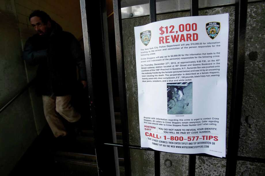 A reward poster is displayed on the entrance to the 40th St-Lowry St Station, where a man was killed after being pushed onto the subway tracks, in the Queens section of New York, Friday, Dec. 28, 2012. Police are searching for a woman suspected of pushing the man and released surveillance video Friday of her running away from the station. (AP Photo/Seth Wenig) Photo: Seth Wenig