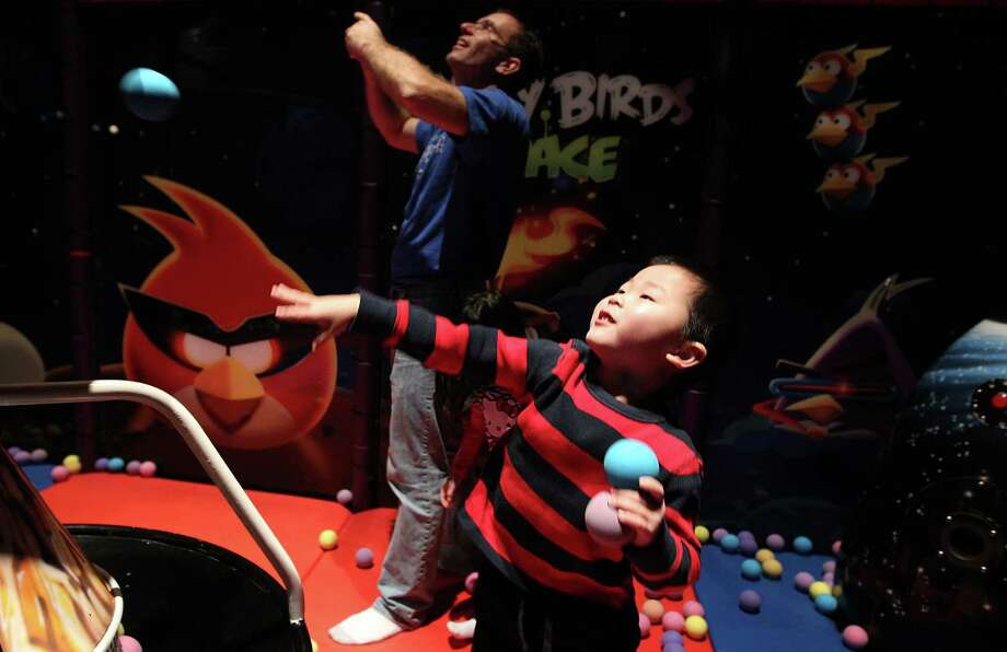 William Song, 4, attempts to throw a ball into a basket inside the Angry Birds Space attraction. Photo: Mayra Beltran, Houston Chronicle / © 2012 Houston Chronicle