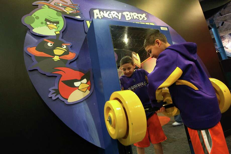 Max Dukes, 9, of Minnesota, uses the 'Angry Birds Weight Lifter' as he attempts to lift weights as if he was in Jupiter. Photo: Mayra Beltran, Houston Chronicle / © 2012 Houston Chronicle