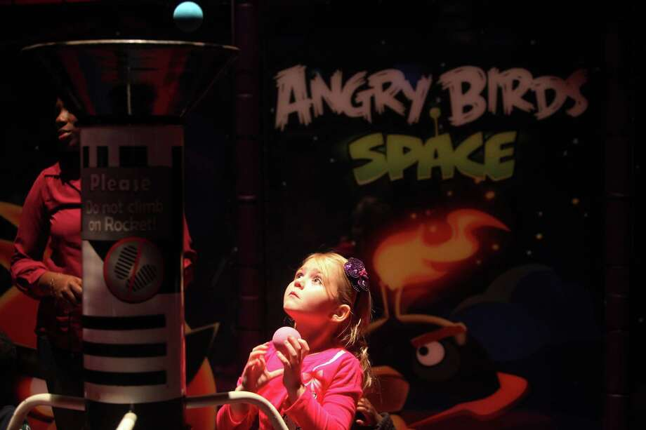Bella Baker, 6, attempts to throw ball into a basket inside the Angry Birds Space attraction. Photo: Mayra Beltran, Houston Chronicle / © 2012 Houston Chronicle