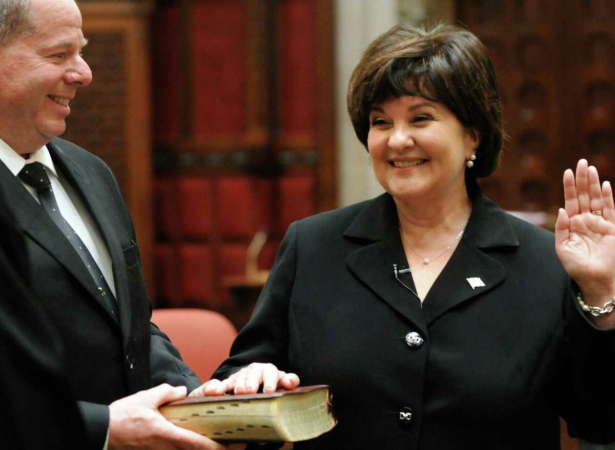 Sen. Kathy Marchione places a hand on the Bible during her swearing in ceremony on Friday, Dec. 28, 2012, at the Capitol in Albany, N.Y. Her husband, Frank, holds the Bible. (Cindy Schultz / Times Union)