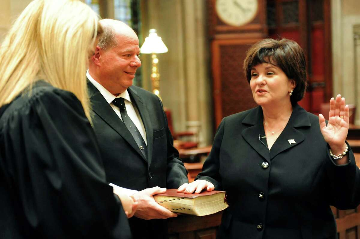 Sen. Kathy Marchione places a hand on the Bible during her swearing in ceremony on Friday, Dec. 28, 2012, at the Capitol in Albany, N.Y. Her husband, Frank, holds the Bible and Judge Anne Crowell administers the oath of office. (Cindy Schultz / Times Union)l