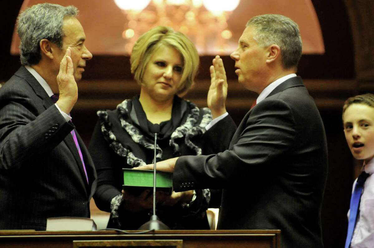 Assembly Majority Leader Ron Canestrari, left, administers the Oath of Office for incoming Assemblyman John T. McDonald III on Friday, Dec. 28, 2012, at the Capitol in Albany, N.Y. McDonald's wife, Renee, holds the Bible. (Cindy Schultz / Times Union)l