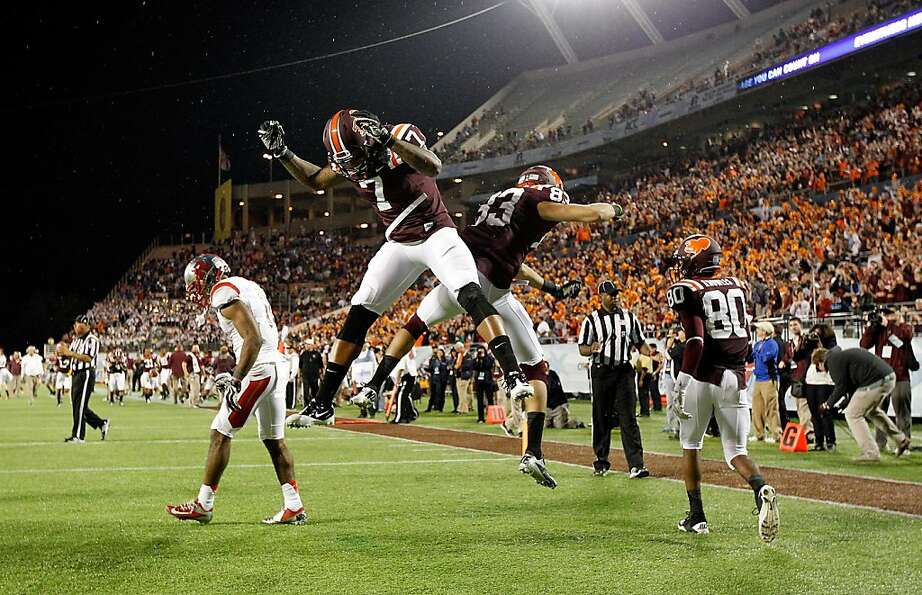 Virginia Tech's Corey Fuller (83) backs into celebrating his game-tying touchdown with Marcus Davis