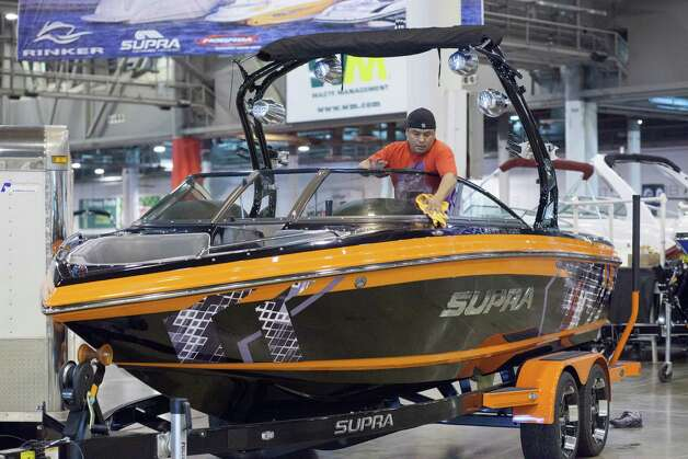 Mike Santana wipes down a ski boat as the Houston Boat Show is set up. Photo: Eric Kayne, For The Chronicle / © 2012 Eric Kayne