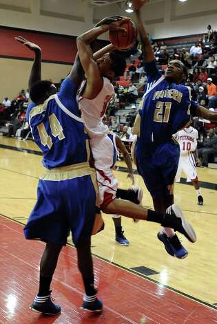 Memorial player Tre'Vaughn Dennis, #33, is shut down by  Ozens  Caleb Wrght, #44, during the Memorial High School Titans basketball game against the Ozen High School Panthers on Friday, December 28, 2012, at the James Gamble Boys Basketball Tournament semi-finals held at Port Arthur Memorial High School. Ozen won over Memorial 69 - 54. Photo taken: Randy Edwards/The Enterprise