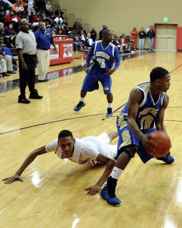 Ozen player Ryan Haynes, #10, steals the ball from a Memorial player leaving him on the ground during the Memorial High School Titans basketball game against the Ozen High School Panthers on Friday, December 28, 2012, at the James Gamble Boys Basketball Tournament semi-finals held at Port Arthur Memorial High School. Ozen won over Memorial 69 - 54. Photo taken: Randy Edwards/The Enterprise