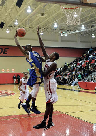 Ozen player Demasters Sam, #15, puts it up for two points over Memorials 6 foot 6 inch Dorian Chatman during the Memorial High School Titans basketball game against the Ozen High School Panthers on Friday, December 28, 2012, at the James Gamble Boys Basketball Tournament semi-finals held at Port Arthur Memorial High School. Ozen won over Memorial 69 - 54. Photo taken: Randy Edwards/The Enterprise