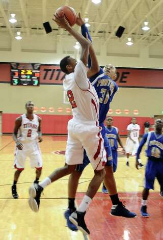 Memorial player Joseph Williams, #12, is fouled by Ozens Charleton Brydson, #30, during the Memorial High School Titans basketball game against the Ozen High School Panthers on Friday, December 28, 2012, at the James Gamble Boys Basketball Tournament semi-finals held at Port Arthur Memorial High School. Ozen won over Memorial 69 - 54. Photo taken: Randy Edwards/The Enterprise