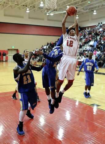 Memorial player Joseph Williams, #12, with a rebound during the Memorial High School Titans basketball game against the Ozen High School Panthers on Friday, December 28, 2012, at the James Gamble Boys Basketball Tournament semi-finals held at Port Arthur Memorial High School. Ozen won over Memorial 69 - 54. Photo taken: Randy Edwards/The Enterprise