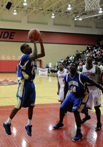 Ozen player Alex Williams, #21, puts it up for two during the Memorial High School Titans basketball game against the Ozen High School Panthers on Friday, December 28, 2012, at the James Gamble Boys Basketball Tournament semi-finals held at Port Arthur Memorial High School. Ozen won over Memorial 69 - 54. Photo taken: Randy Edwards/The Enterprise