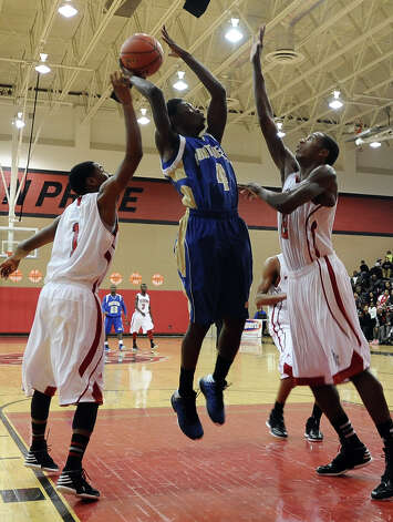 Ozen player Kourtney Williams , #4, puts it up for two during the Memorial High School Titans basketball game against the Ozen High School Panthers on Friday, December 28, 2012, at the James Gamble Boys Basketball Tournament semi-finals held at Port Arthur Memorial High School. Ozen won over Memorial 69 - 54. Photo taken: Randy Edwards/The Enterprise