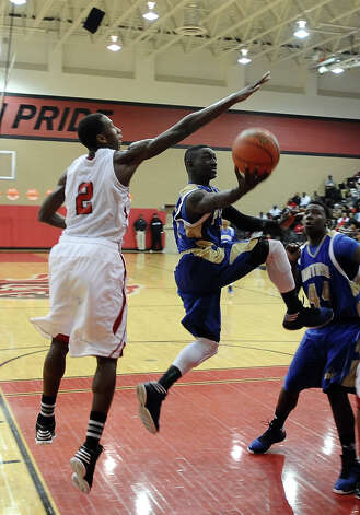 Ozen player Jordan Hunter, #23, puts it up for two during the Memorial High School Titans basketball game against the Ozen High School Panthers on Friday, December 28, 2012, at the James Gamble Boys Basketball Tournament semi-finals held at Port Arthur Memorial High School. Ozen won over Memorial 69 - 54. Photo taken: Randy Edwards/The Enterprise