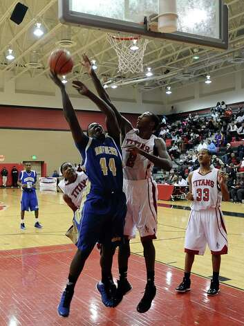 Ozen player Caleb Wright, #44, is fouled while putting it up for two during the Memorial High School Titans basketball game against the Ozen High School Panthers on Friday, December 28, 2012, at the James Gamble Boys Basketball Tournament semi-finals held at Port Arthur Memorial High School. Ozen won over Memorial 69 - 54. Photo taken: Randy Edwards/The Enterprise