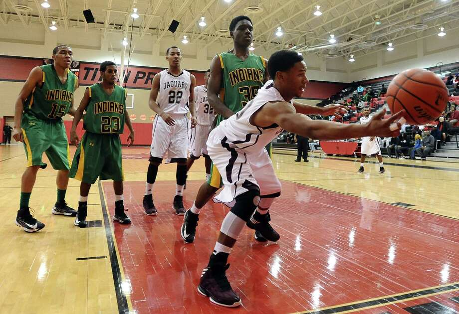 Central player Garrison Mitchell, #10, saves the ball from heading out of bounds during the Central High School Jaguars basketball game against the Washington-Marion High School Charging Indians on Friday, December 28, 2012, at the James Gamble Boys Basketball Tournament semi-finals held at Port Arthur Memorial High School. Central won over Washington-Marion 60- 42. Photo taken: Randy Edwards/The Enterprise