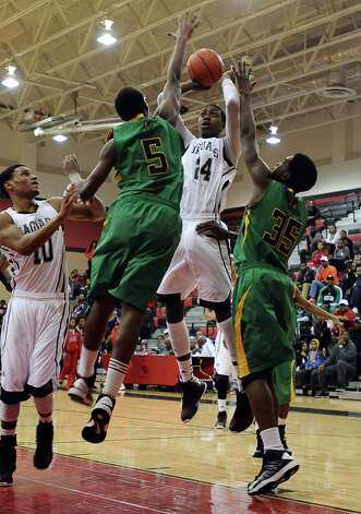 Central player E'Torrion Wilridge, #24, is fouled while putting it up for two during the Central High School Jaguars basketball game against the Washington-Marion High School Charging Indians on Friday, December 28, 2012, at the James Gamble Boys Basketball Tournament semi-finals held at Port Arthur Memorial High School. Central won over Washington-Marion 60- 42. Photo taken: Randy Edwards/The Enterprise