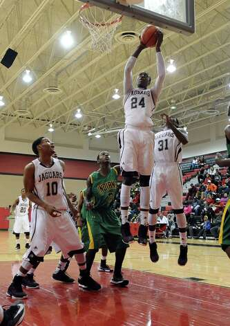 Central player E'Torrion Wilridge, #24, gets the rebound on a wild shot during the Central High School Jaguars basketball game against the Washington-Marion High School Charging Indians on Friday, December 28, 2012, at the James Gamble Boys Basketball Tournament semi-finals held at Port Arthur Memorial High School. Central won over Washington-Marion 60- 42. Photo taken: Randy Edwards/The Enterprise