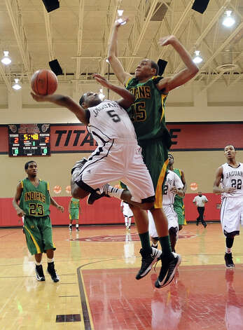 Central player Jacory Guillory, #5, is fouled while making a drive to the goal during the Central High School Jaguars basketball game against the Washington-Marion High School Charging Indians on Friday, December 28, 2012, at the James Gamble Boys Basketball Tournament semi-finals held at Port Arthur Memorial High School. Central won over Washington-Marion 60- 42. Photo taken: Randy Edwards/The Enterprise