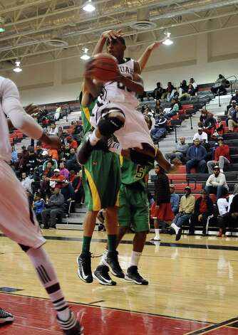 Central player Dominique Harrison, #20, attempts to put it up for two and is shut down during the Central High School Jaguars basketball game against the Washington-Marion High School Charging Indians on Friday, December 28, 2012, at the James Gamble Boys Basketball Tournament semi-finals held at Port Arthur Memorial High School. Central won over Washington-Marion 60- 42. Photo taken: Randy Edwards/The Enterprise