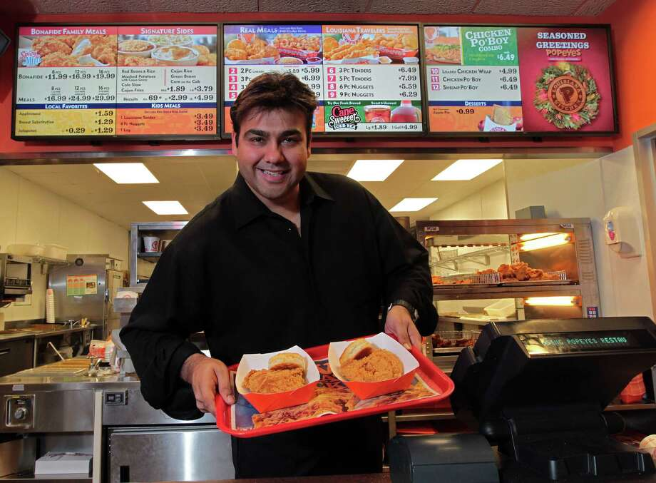 "Amin Dhanani will be remaking many of his Popeyes locations to create more contemporary dining rooms and other improvements. ""The Popeyes brand is on an upswing,"" he says. Photo: James Nielsen, Staff / © Houston Chronicle 2012"