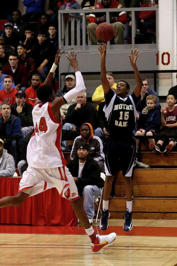 Mike Ross Connecticut Post freelance -Notre Dame of Fairfield #15 Jesse McIntosh sucesfully shots a three point play over Fairfield Prep's #44 Paschal Chukwu during second half action at Friday evening Holiday Classic held at Alumni Hall at Fairfield University. Photo: Mike Ross / @www.mikerossphoto.com