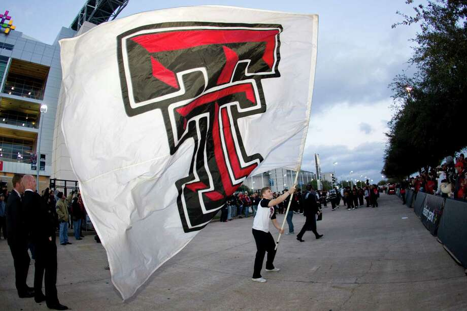 A Texas Tech cheerleader waves a double T flag to get the crowd ready for  the Meineke Car Care Bowl college football game, Friday, Dec. 28, 2012, outside Reliant Stadium in Houston. Photo: Nick De La Torre, Houston Chronicle / © 2012  Houston Chronicle