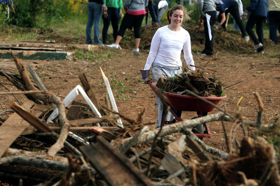 In this photo taken Oct. 19, 2011, Notre Dame fencer Kat Palazzoto pushes a wheelbarrow with debris as she helps cleanup tornado debris in Tuscaloosa, Ala. Twenty-four student athletes from Notre Dame were in Tuscaloosa volunteering time during their fall break to help clean up tornado damaged areas. (AP Photo/The Tuscaloosa News, Robert Sutton) Photo: Robert Sutton