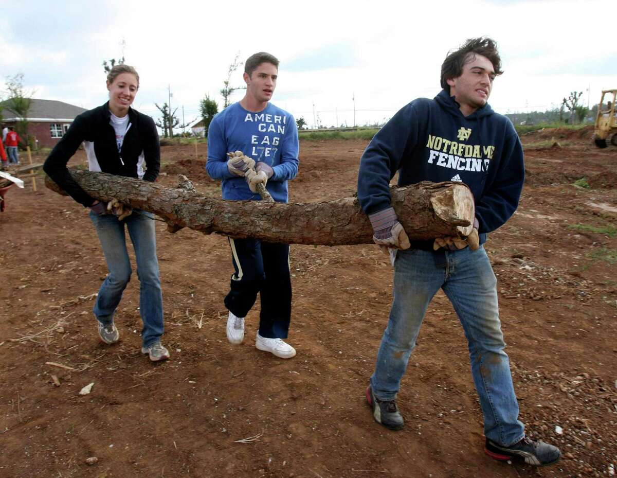 In this photo taken Oct. 19, 2011, Notre Dame track athlete Natalie Geiger, left, and fencers Michael Rossi and Gabriel Acuna help carry a large tree branch to the road in Tuscaloosa, Ala. Twenty-four student athletes from Notre Dame were in Tuscaloosa volunteering time during their fall break to help clean up tornado damaged areas. (AP Photo/The Tuscaloosa News, Robert Sutton)
