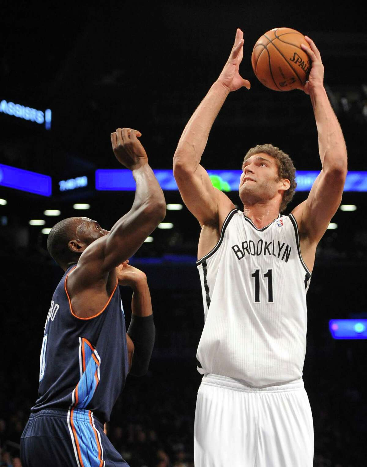 Brooklyn Nets' Brook Lopez (11) shoots over Charlotte Bobcats' Bismack Biyombo (0) in the first half of an NBA basketball game on Friday, Dec., 28, 2012 at Barclays Center in New York. The Nets won 97-81. (AP Photo/Kathy Kmonicek)
