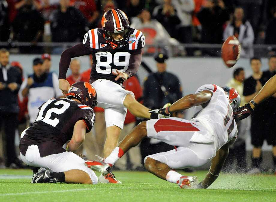 Virginia Tech kicker Cody Journell (89) gets the hold from quarterback Trey Gresh (12) while booting the go-ahead field goal in overtime in front of Rutgers defensive back Logan Ryan (11) during an NCAA college football Russell Athletic Bowl game on Friday, Dec. 28, 2012, in Orlando, Fla. (AP Photo/Brian Blanco) Photo: Brian Blanco
