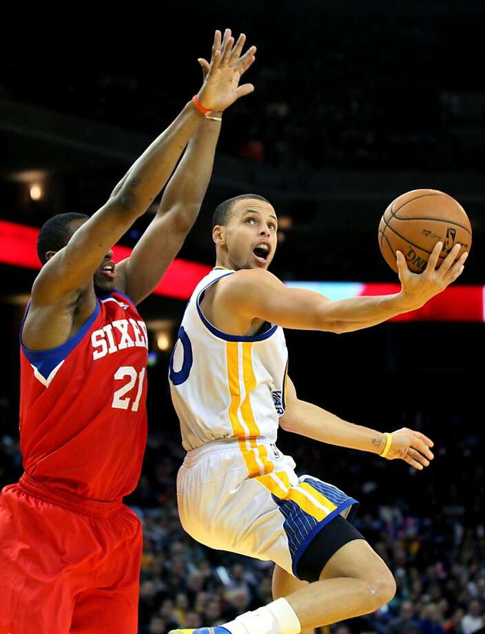 Stephen Curry, who scored 11 points for the Warriors, finds a path to the basket against Philadelphia's Thaddeus Young in the first half. Photo: Lance Iversen, The Chronicle